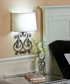 """Turn this Scrolled Metal Wall Lamp on and off from across the room. Remote-controlled LED light highlights beautiful scrollwork. The white half-shade pops against the black metal. Requires 3 """"AA"""" batteries. 16"""" x 11"""" x 5-3/4"""". Polystyrene."""