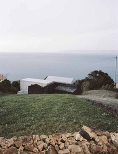 "Initially unassuming, the E/C home appears hidden from the road, perched on the sloping edge of the island and partially wrapped in the basalt walls from an 18th-century farmhouse. Architect Ines Vieira da Silva approached the site with a vision to create a relationship with the landscape; he designed the 2,600-square-foot holiday home to not only be a simple escape, but also to frame the weathered coast and reflect its past. ""Both paths to the house were designed with basalt stone, as if…"