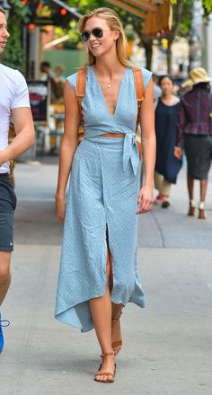 Karlie let her gorgeous blue wrap dress take center stage, completing it with neutral casual accessories, including a backpack and flat studded sandals. Image Source: FameFlynet