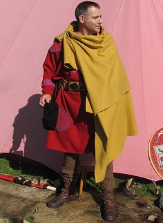 The sagum cloak is fastened at the right shoulder with a crossbow brooch of gilded silver. The large size of the cloak means in this case the cloak is doubled over the shoulders.