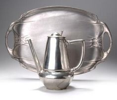 "Art Nouveau pewter serving tray, c. 1904, and a coffeepot, in the style of Friedrich Adler, tray marked ""URANIA"", 48.3 cm. long, coffepot marked ""URANIA 1106"", 22.8 cm high"