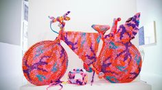 The work of OLEK, born Agata Oleksiak in industrial Poland, explores sexuality, feminist ideals and the evolution of communication through color, conceptual exploration and meticulous detail. OLEK consistently pushes the boundaries between fashion, art, craft and public art—fluidly combining the sculptural and the fanciful. With the old fashion technique of crocheting, she uses the ephemeral medium of yarn to express everyday occurrences, inspirations and creating a metaphor for the...
