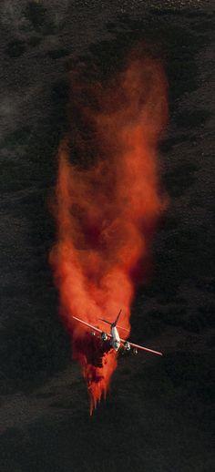 A plane dumps retardant on the fire in the foothills above Herriman on Friday, June 29, 2012. (Jeremy Harmon     The Salt Lake Tribune)