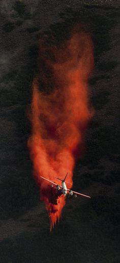 A plane dumps retardant on the fire in the foothills above Herriman on Friday, June 29, 2012.