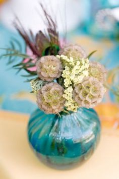 I love this flower arrangement idea! Love the peacock feather and the aqua vase :)