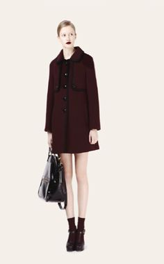 Heavy Wool Raglan Coat Burgundy A winter coat like no other. Beautiful heavy wool with fabulous retro detailing in the form of large shiny buttons and a wide over sized collar. Stand out and be seen in this Orla Kiely raglan coat, just add a vintage clutch to complete the look. Available in black and burgundy.