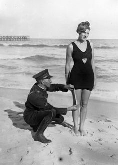Officer from the West Palm Beach police force measuring the bathing suit of Betty Fringle on Palm Beach to ensure that it conforms with regulations introduced by the beach censors .