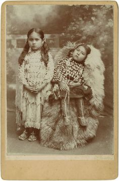 Native American:Photography, Cabinet Card - A studio portrait of two young Kiowa girls. Circa1885. Length 6 1/2 in. Width 4 1/4 in.. Both girls are we...