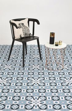 This traditional Portuguese tile flooring design features a tile effect in powder blue colour, contrasting with clean white and black decorative shapes.
