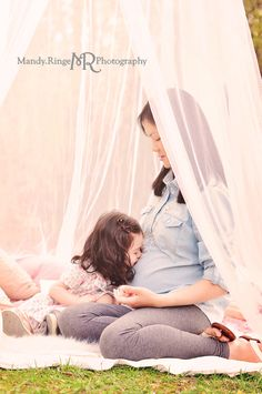 Styled Mommy & Me mini sessions. The scene includes a blanket layered with white faux fur, pink, gold and gray pillows, and a white hoop canopy hanging from a tree.