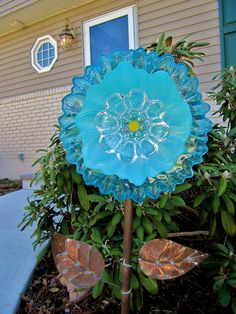 Beach colors of aqua and yellow predominate this pretty garden ornament! It has been carefully created with used glass items found in thrift and antique stores, only the best quality are chosen. This one is approx. 10 inches in width, I have   used quality arts glass paints to color the vintage snack plate in the rear. It has been baked on for adhesion and outdoor conditions. To stake this flower outside in the garden, you need a length of copper tubing or iron rebar. Available in any   Home…