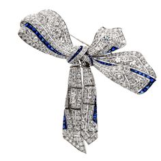 This Fine Circa 1910 Era Brooch is Finely Crafted in Solid Platinum. It is accented with 4 genuine round old European-cut diamonds approx. 2.85 carats in total, all F-G color, VS clarity. The bow with movable tassel is covered with some 318 genuine round old European-cut diamonds approx. 24.15 ct, G color, VS clarity and 62 cal liberated square cut royal blue genuine sapphires approx. 10.00ct. This antique brooch pin has exquisite mille grain, floral open work, and a flexible ribbon.