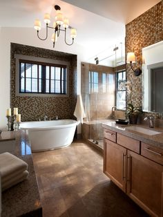 Mosaic tile walls give this spacious master bathroom an artful look, bringing in color and texture to the space. Candles by the bathtub create a relaxing atmosphere, while windows above the tub and in the glass walk-in shower flood the space in natural light.