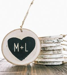 Trim the tree with a sweet ode to someone special this year with this personalized couple ornament. This rustic wood ornament features a heart inscribed with two initials, for a romantic addition to the tree. The design is painted by hand on a slice of birch wood and hangs from a length of twine, to add to the Christmas tree year after year.