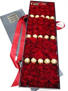 Ruže i ferrero roche u crnoj izduženoj kutiji.