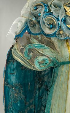 """Costume:Gabriella Pescucci in 1998. """"Queen Titania"""". organza is in tones ranging from ivory to teal, with the central panel embroidered chenille yarns, golden threads and green stones.The mantle, with its interior of blue georgette fabric all gold and silver wire, consists on the combination of large edges and silk embroidered inserts with large pleated blue silk drapes. The embroidery, are a variety of materials including: chenille wires, wires gold, azure stones and nylon tulle. Detail"""
