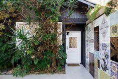 A entrada do ateliê da artista Calu Fontes tem painel de azulejos e fachada com…
