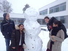 Årest første snø har kommet til Lambertseter og noen driftige elever har laget en enorm snømann i atriet. Elevene på bildet er mot(villige) posører, men hvem har laget snømannen, mon tro?