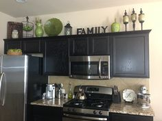 Home decor.  Decorating above the kitchen cabinets.  Kitchen decor.  Green, black, brown color scheme.