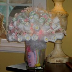 Diaper Bouquet~diapers are rolled around wooden skewers and secured with clear rubber bands, and then pushed into a foam ball which is hidden and wedged into the vase. Accent with tulle. Cute for a baby shower gift Idee Baby Shower, Shower Bebe, Baby Shower Gifts, Diaper Shower, Girl Shower, Diaper Bouquet, Rose Bouquet, Baby Bouquet, Diaper Wreath