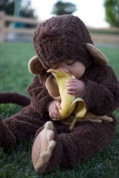 Haha - baby in a monkey suit chowing on a nanner