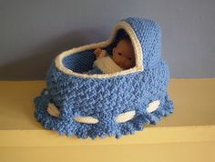 "This knitted cradle, complete with a set of matching bedding, will fit a 5"" baby doll or similar size toy. The sides of the cradle fold up over the doll to make a bag and drawstrings keep everything safe inside. An ideal present for a child who can't leave home without a doll."