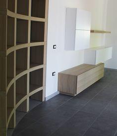 Arredo su misura per abitazione privata realizzato da Trova&Rinnova. La libreria in legno segue il disegno curvo delle piastrelle del pavimento bicolore e del controsoffitto.