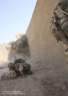 A Paratrooper from 5 Platoon, B Company, 3rd Battalion the Parachute Regiment takes cover after throwing a grenade at a Taliban enemy position during Operation Oqab Tsuka in Helmand Province, Afghanistan.