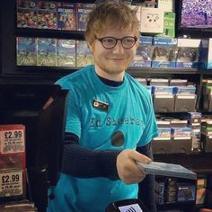 Ed Sheeran...wearing an Ed Sheeran shirt...with a name tag that says Ed...selling the new Ed Sheeran album. How's that for meta? Lol