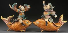 A PAIR OF CHINESE GLAZED POTTERY ARCHITECTURAL ROOF TILES, 18TH/19TH CENTURY. Of figural form depicting two fanciful males riding atop goldfish. Height 12 inches (30 cm).