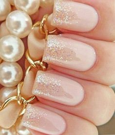 nails painted pink and covered with clear glittery polish