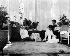 Grand Duchess Anastasia sits with her mother, Alexandra, and sister Olga in her mother's sitting room. Russia, ca. 1916.