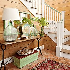 Hand-blown glass lamps and jars in sea glass shades, a nautical map, and a few seashells look collected and personal, not themed. The seafoam green painted stair railing is another subtle seaside touch.