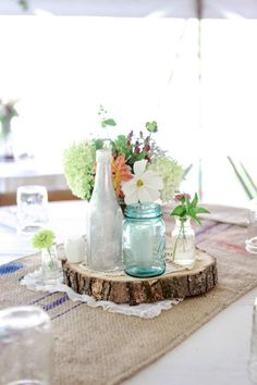 Simple country chic centerpieces with wood slices, blue hued mason jar, vintage bottles & wild flowers | Rustic Boho Chic Country Wedding With Stunning Wild Flowers & Barn Perfect For Bluegrass Dancing | Photograph by Dan and Melissa Photography  http://www.storyboardwedding.com/rustic-boho-chic-wedding-wild-flower-barn/