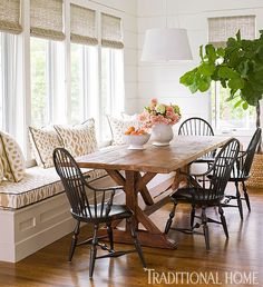 Traditional dining table and chairs with a long window seat and grass shades. California Casual style