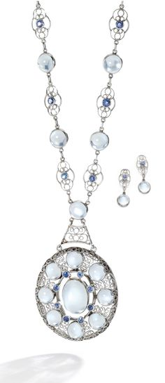 Louis Comfort Tiffany - An antique moonstone and sapphire demi-parure, circa 1910-20. Comprising; a pendant necklace and a pair of earrings; the oval pendant set with cabochon moonstones and circular-cut sapphires, within a scrolled wirework surround, to a similar neckchain, length approximately 460mm, signed Tiffany & Co.; the earrings of matching design, post and butterfly fittings.