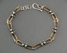 I made this bracelet from brass and sterling silver. The brass forged-loop pieces are linked with heat-formed sterling rivets. The bracelet has great