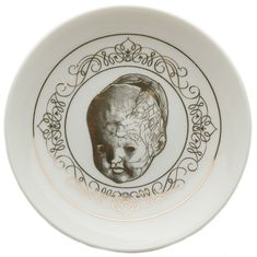 DETAILS:  This trinket dish is a perfect catch-all for loose coins, jewelry and any other small, vagabond items in need of a home. It features a creepy, antique doll head illustration surrounded by filigree, printed in metallic gold on a white porcelain dish. Put one by your sink, dresser, night stand or wherever you need it!
