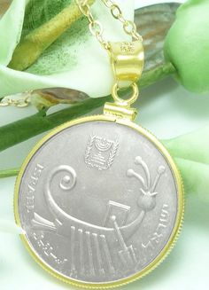 A 10 Sheqalim Israel coin pendant, image of an ancient galley and the Emblem of the State of Israel mounted in a 14kt gold filled bezel and suspended by a 14kt gold filled 19 inch chain necklace.  Obv