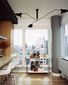 Kitchen - A Serge Mouille three-arm light fixture above a tray of bar essentials