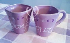 pair of light purple mug with written BONJOUR and small hearts in white and purple