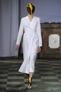 WHITE BLOUSE: A classic Maison Martin Margiela blouse is reinterpreted in embroidered cloth dating from the 19th century. Production time: 28 hours. Linen cloth sourced in the Hautes-Pyrénées, France