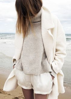 Winter white coat, linen white shorts, and knitted chunky sweater