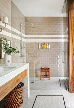 The shower fittings, shower shelf, teak stool, and mosaic-tile flooring in one guest bath in this Los Angeles home by Dan Fink are all by Waterworks   archdigest.com