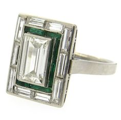 Exquisite Art Deco Emerald Diamond Platinum Engagement Ring. 1920s Art Deco platinum engagement ring, featuring an emerald cut center diamond, approximately 2ct VS1-H, surrounded with ten baguette cut diamonds and emeralds. Ring is a size 6 3/4, ring top is 17mm x 15mm. Weight - 8.8 grams c 1920s