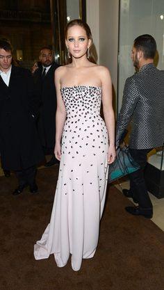 Jennifer Lawrence de Dior en blanco con toques brillantes y con el pelo peinado hacia atrás.
