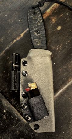 Armatus Carry Solutions Woodsman custom bush craft sheaths.  This one was built for an ESEE 4 and features a taco-style fold over sheath for enhanced durability, attachments for a mini bic lighter and an Olight i3s mini torch, and a tech lock for the belt attachment.