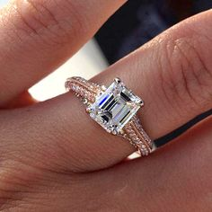 emerald-cut stone sitting on a rose gold band flanked by two rows of small diamonds.
