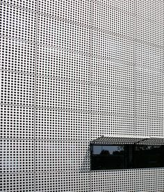 Office building with uniformly perforated facade panels and folding shutters | Photo © RMIG