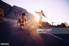 Stock Photo : Friends longboard skating on road sunset